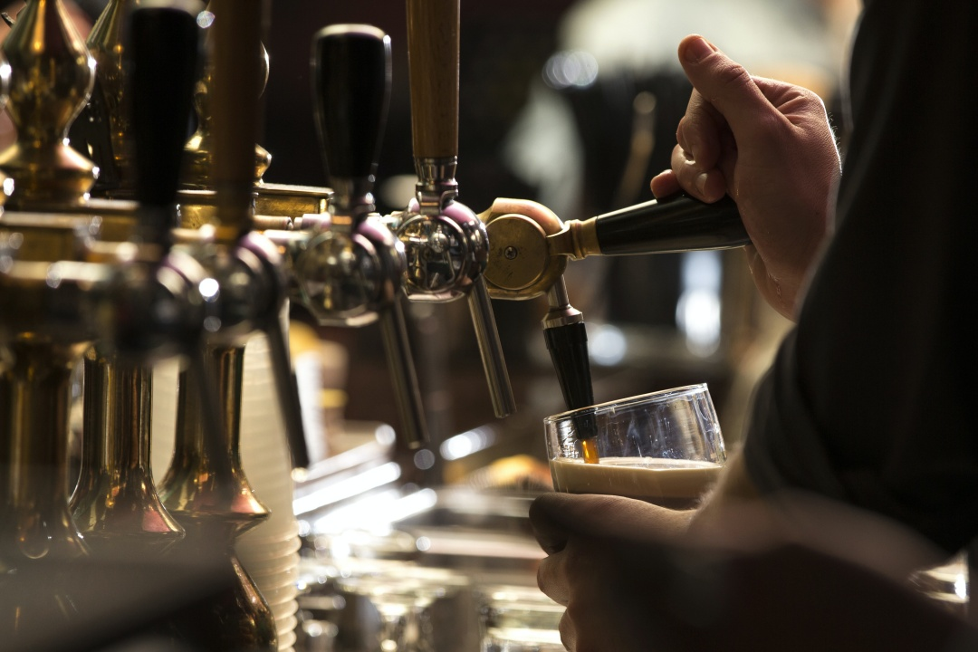 pub worker pulling a pint