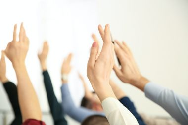 People's hands raised as though asking questions