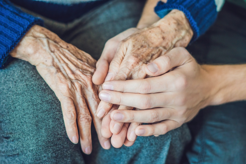 Carer holding elderly woman's hand