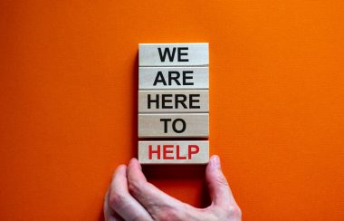 Wooden blocks with message 'we're here to help'