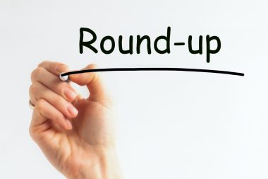 Hand with pen writing the word round-up