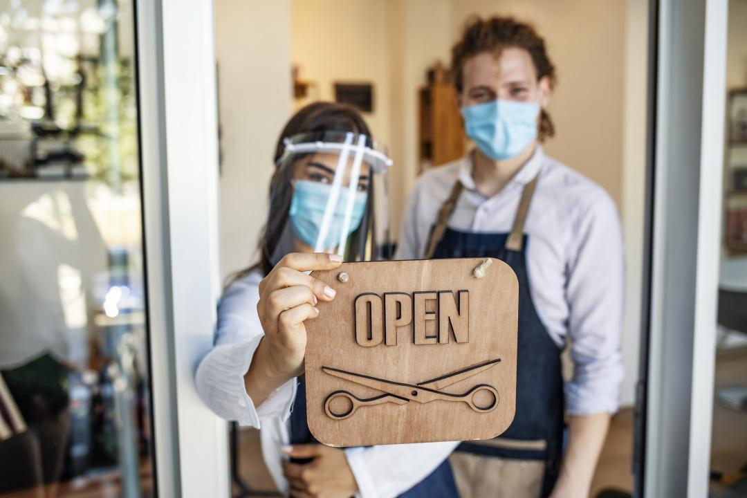 Hairdresser holding up an 'open' sign