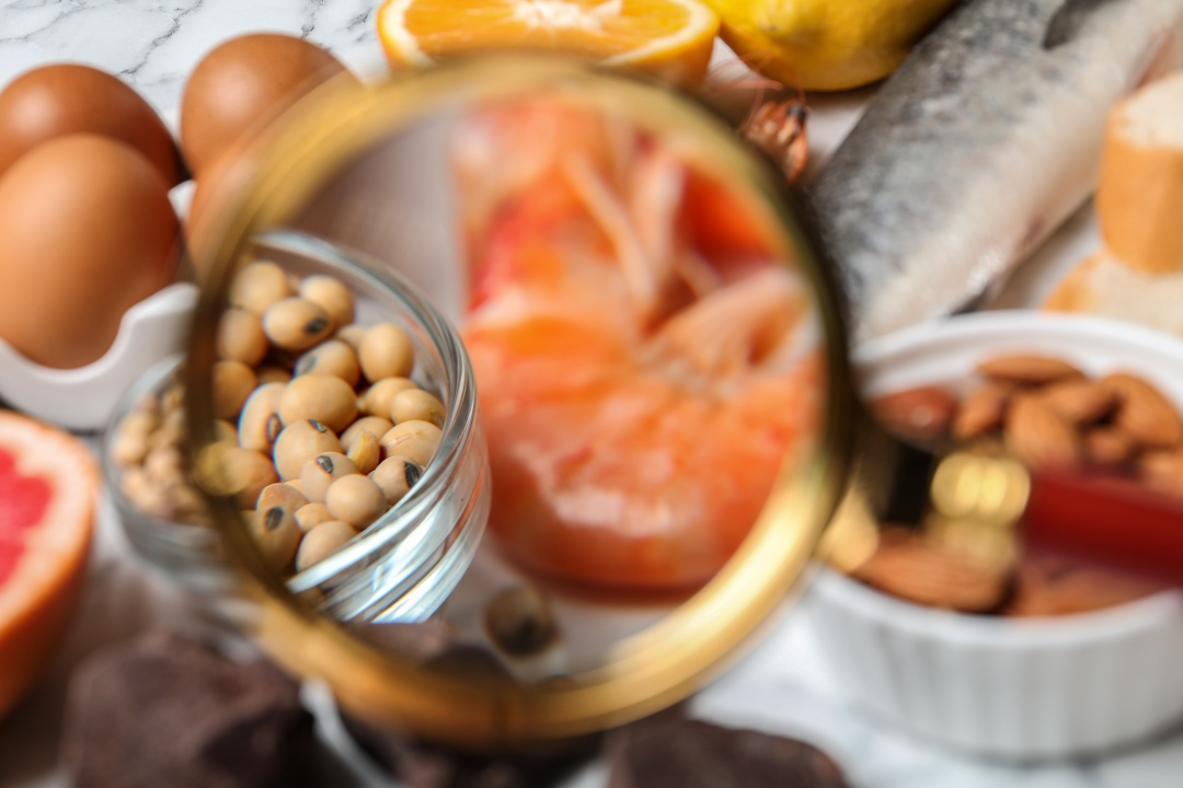Different products with magnifier focused on shrimps and soy beans, closeup. Food allergy concept